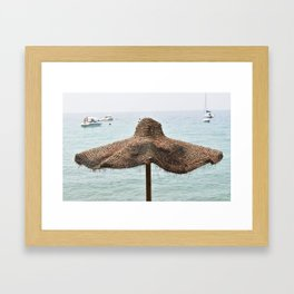 Beach umbrella in natural fibers on the shore of Lake Garda Framed Art Print