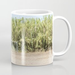 Door and soccer field with dry sand during summer Coffee Mug