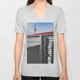 steel fence and wooden fence with red building in the city Unisex V-Neck