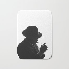 Silhouette of private detective in old fashion hat lights a cigarette Bath Mat