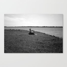 Bench by the waters edge. Canvas Print