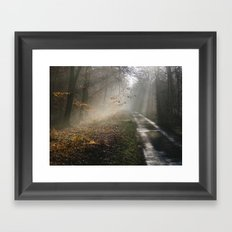 Remote country road through mist and woodland at sunset. Norfolk, UK. Framed Art Print