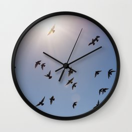 Flock of birds flying against blue sky and bright sun Wall Clock