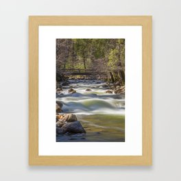 A bridge over the Merced River stands solidly over the velvety exposure of the water Framed Art Print