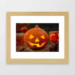 Burning Jack O'Lantern on a rustic table with autumn decorations Framed Art Print