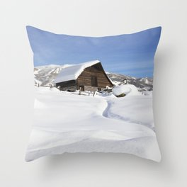 Heavy snow surrounds and lies a top a cabin in Steamboat Springs Colorado Throw Pillow