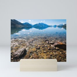 Snow-capped mountains view in summer from the rocky shore of lake Wakatipu. Mini Art Print