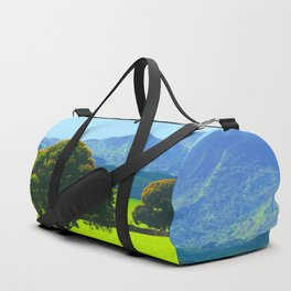 green tree in the green field with green mountain and blue sky background Duffle Bag