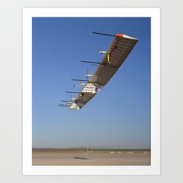 972. The Atmospheric Turbulence Measurement System booms extend forward from the Pathfinder-Plus solar wing as it soars over Rogers Dry Lake. Art Print