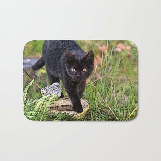 Lovely black cat walking her garden Bath Mat