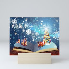 Magic book with decorated Christmas tree and Santa riding a sleigh Mini Art Print