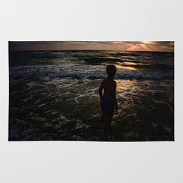 Boy looking at the sunset Rug