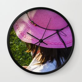 Big pink hat for a child girl on the grass Wall Clock