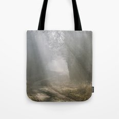 Sunlight through mist along a remote country track. Norfolk, UK. Tote Bag