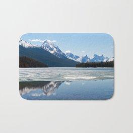 Rocky mountains reflecting in Maligne lake Bath Mat