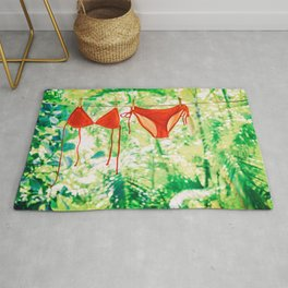Red bikini hanging on clothes line drying. Rug