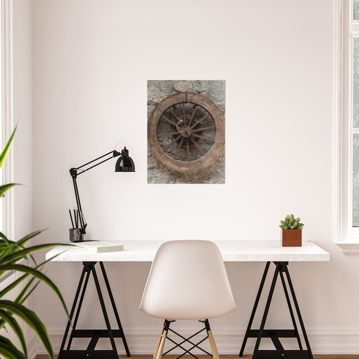 Wooden wheel hanging on a stone wall Poster
