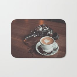 A cup of hot cappuccino placed on a table next to the old camera with lens and coffee beans Bath Mat