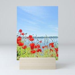 Red poppies in the lakeshore Mini Art Print