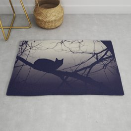Mistery cat perching on tree in misty night Rug