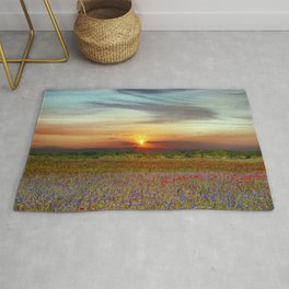 Red poppies and bluebells amid the setting sun Rug