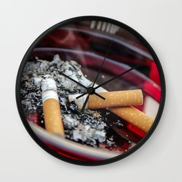 A ruby-colored glass ashtray contained three used cigarette butts along with their ashes A healthcar Wall Clock
