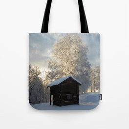 Snowy cabins and light in the trees Tote Bag
