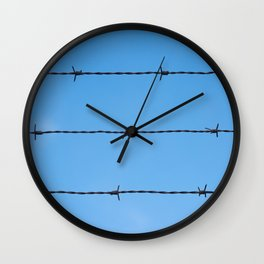 Contseptual shot of barbed wire over blue sky Wall Clock
