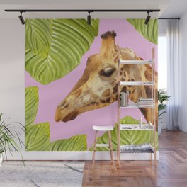 Giraffe with green leaves on a pink background Wall Mural