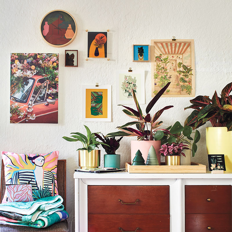 credenza with plant themed gallery wall above it