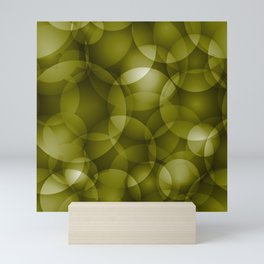 Dark intersecting translucent olive circles in bright colors with an oily glow. Mini Art Print