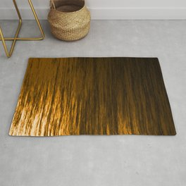 Bright texture of shiny foil of bronze flowing waves on a dark fabric. Rug