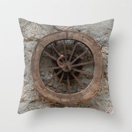 Wooden wheel hanging on a stone wall Throw Pillow