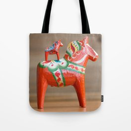 Two Dalahorses in different sizes standing on rustic wooden table Tote Bag