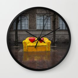 Two red hearts on yellow couch with orange flowers Wall Clock