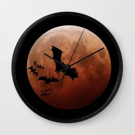 Black bats flying against a red moon Wall Clock