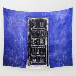 Black worn out door on blue wall Wall Tapestry