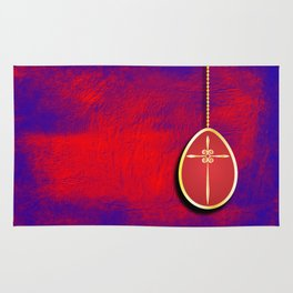 Gold cross in red egg hanging against a rich red and purple Rug