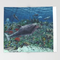 Dolphins play in the reef Throw Blanket