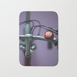 Red bell on purple Bath Mat