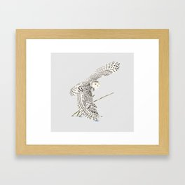 The snowy owl in flight with his wing touching the snow Framed Art Print