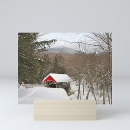 Red covered bridge in snowy landscape Mini Art Print