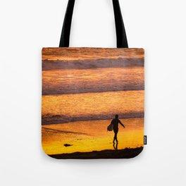 Surfer walking along beach at sunset Tote Bag