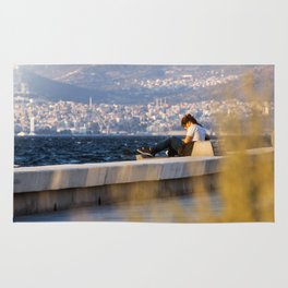 Girl sitting on a bench at seaside in Izmir (Turkey) Rug