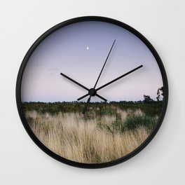 Moon and twilight sky over open area of felled forestry land. Norfolk, UK Wall Clock