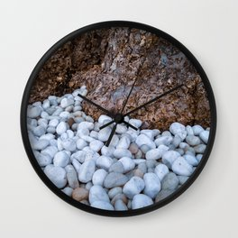 White stones by a tree trunk Wall Clock