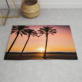 Orange bright sunset at the beach between palms Rug