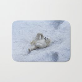 Portrait of polar bear cub practicing yoga on the snow. Bath Mat