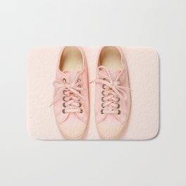Pink canvas sneakers on pink background, close up Bath Mat