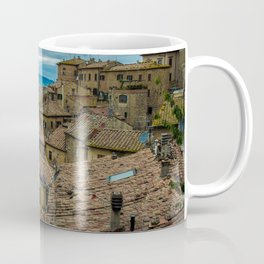 Mountain village with reddish roofs. Cloudy sky over the mountains. Coffee Mug